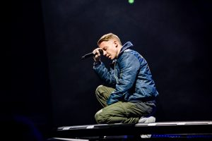 Macklemore kneels with his eyes closed and a microphone leaned against his head during a song.