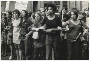 Black and white photo of female activists linking arms at a women's march, 1970