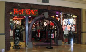 The front of the retail store Hot Topic. Hot Topic is written in kind of creepy red text and the entrance to the store is a dark archway. In the indow is a show with a skull on it, and the inside looks dark and boasting with merchandise.