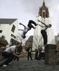 Multiple exposure shot showing a young traceur, in three stills, performing a backflip from a stone bench.