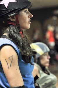 Roller derby participant with a star on her helmet and the number 17 on her arm looks to the right.
