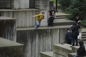 A young traceur is leaping off a large concrete wedge, watched by a small group of other traceurs.