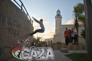 "As the sun sets in the background, a traceur jumps onto a wall, casually observed by a few young people. The image is stamped with a mark that says ""Parkour Jumper Gaza"""