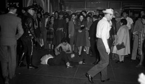 This image shows a pachuco on the ground, being stripped of his clothing and being beaten. There are numerous people watching this take place.