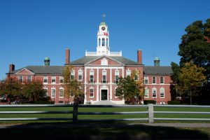 Wide shot of a red brick building with a white tower on Phillips Exeter's campus in New Hampshire