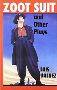 "A flyer for the play by Luis Valdez, titled ""Zoot Suit"", shows a pachuco in a zoot suit, a fedora hat, a chain hanging from his waist and a necklace with a cross on it."