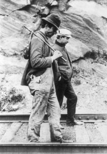 Black and white photo of two older men walk down train tracks in front of stone and they are dark gray wearing jackets. One wears a black fedora and is carrying a rucksack and the other wears a white conductor hat.
