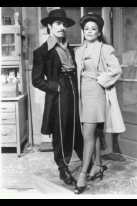 A photo in a black and white color scheme showing a pachuco and a pachuca. He is wearing a fedora, baggy pants and coat, along with a very long chain tied at his waist. She is also wearing a long coat, with a skirt and high heels.