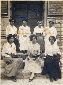 A black and white image of African American women sitting on the steps up to a building.