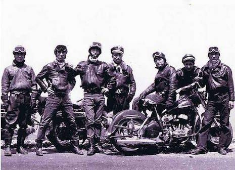 Black and white group photo of seven kaminari zoku dressed in old-fashioned leather jackets, jeans, and riding goggles. Some members sit or lean against the two motorcycles present.