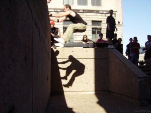 a traceur, surrounded by observers, is shown leaping onto a wall, hanging on to the top by their hands