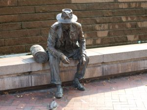 A bronze statue of a man sitting wearing an overcoat and wide brimmed hat. There is a bronze rolled blanket next to him and he is staring at a tiny bronze duck by his left foot.