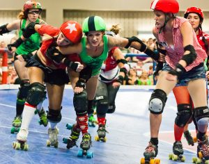 Skaters wearing green and red uniforms attempt to block and pass one another.