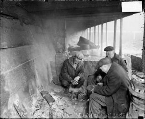 Three older men sit in a circle in a broken down building. They are all wearing black jackets and gray fedoras.