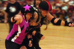 In the midst of a roller derby bout, one skater goes to shoulder block the opposing team's jammer.