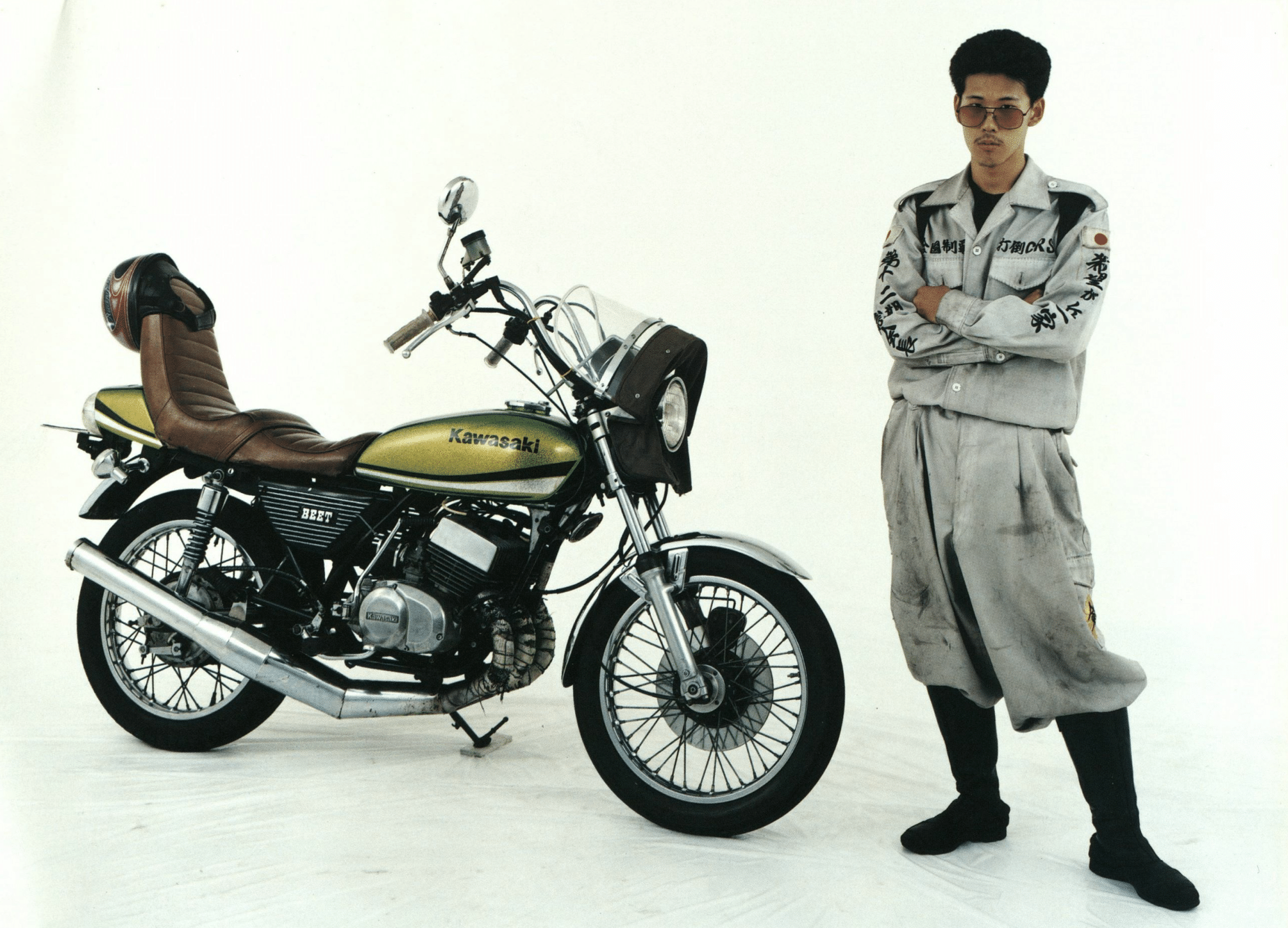 A bōsōzoku member wearing a white tokkōfuku and intimidating expression stands with arms crossed next to his modified Kawasaki motorcycle. The motorcycle has a yellow paint-job, inward-bent handles, extremely large muffler, and a tall, brown leather seat.
