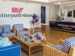 Interior of a Vineyard Vines clothing store decorated with colorful chairs and a large image of the Vineyard Vines company logo.