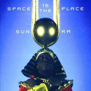 Album cover for Sun Ra's 'Space is the Place' album. The cover features a Black man against blue background. The manis wearing a head peace that lis round with two light holes for a head (it looks like an alien), and he is also wearing an Ancient Egyptian costume. (
