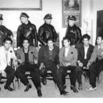 This image shows six pachucos being held in custody by police officers. It is in a black and white color scheme.
