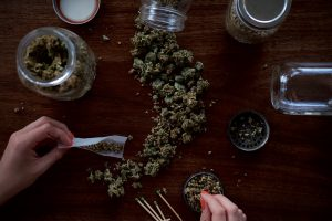 overhead shot of a hand preparing a blunt, there is a line of marijuana down the image