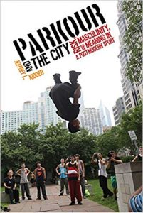 A small crowd watches a young man midmotion. He is upside down holding his knees in air, in front of an urban landscape
