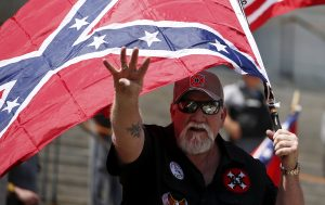Bearded white man carries a large Confederate flag and raises four fingers