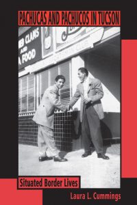 The cover to Laura Cummings' book shows two pachucos shaking hands in front a food establishment. The picture is in black and white.