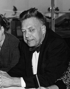 Alfred Kinsey 1955. An older white man is hunched over a table with hands closed into each other.