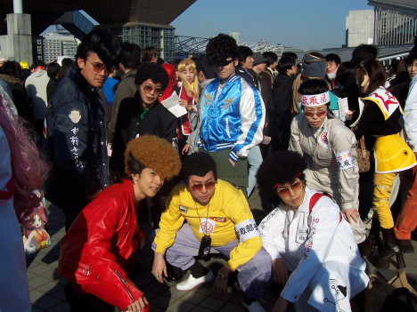 Group photo of young men at a convention dressed-up as highly exaggerated versions of bōsōzoku. They look like characters from an anime or video game more than actual people.