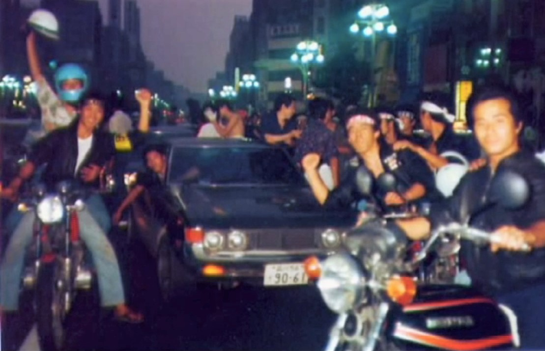 Blurry image of smiling bōsōzoku at Doukoho, one of the largest runs in bōsōzoku history.