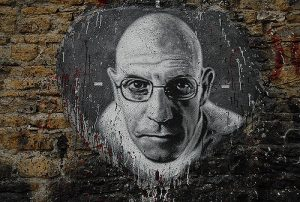 A black and white painting of a bald man with glasses done on a tan brick wall with black paint in the bottom right corner..