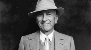 Black and white image of an older white man smiling and dressed in a suit and fedora.