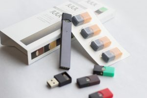 A black rectangular vape is show, called a JUUL, with a charger and multiply nicotine pods strung about.