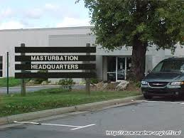 "There is a white office building with dark green van parked on the right and a tree next to it. A sign made from wooden boards outfront reads in all capital letters, ""Masturbation Headquarters""."