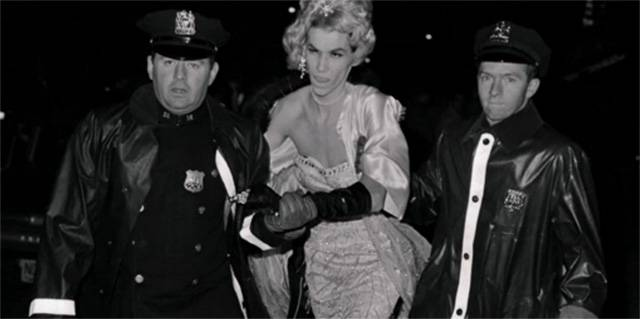 A protester wearing jewelry, long black gloves, and a lovely dress is flanked on both sides by policemen.