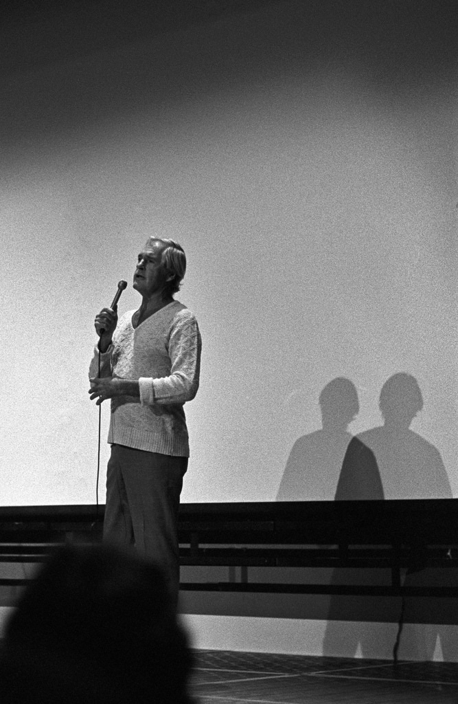 A black and white photo of a simlpl-dressed man giving a speech