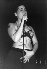 "Woman singing into microphone wearing a bra with ""slut"" written across her stomach"
