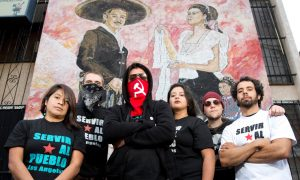 A group of activists stand in front of a mural. Some have their face covered. They are visibly diverse and form a V shape.