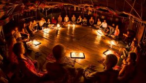 People sitting in a circle during an ayahuasca ceremony in Peru.