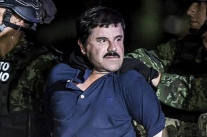 "Arresting of a man known as ""El Chapo"" who is dressed in a blue shirt and being taken away by men in uniform."