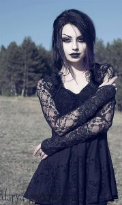 A goth woman stands with arms crossed, presumably outdoors