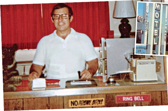 A white man in a button up short sleep white shirt mans the desk of a hotel. He smiles with a stamp in hand.