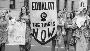 "Black and white photo of women holding a banner that says ""equality the time is now"""