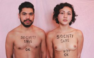 "A man and woman, shown topless with ""society says ok"" written on the man's chest and ""society says not ok"" on the woman's chest"