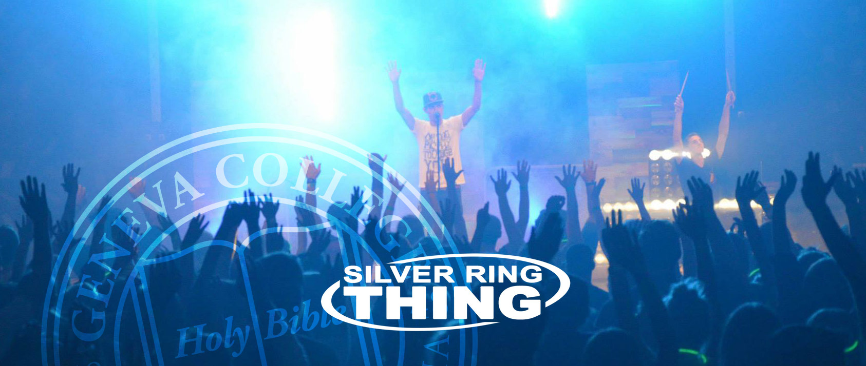 A white man wearing a fedora stands in from of a crowd of people with his hands in the air. At the bottom of the image it reads Silver Ring Thing.