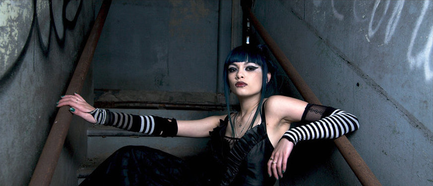 A woman wearing all black and dark makeup sits in a staircase. She is looking into the camera with no facial expression.