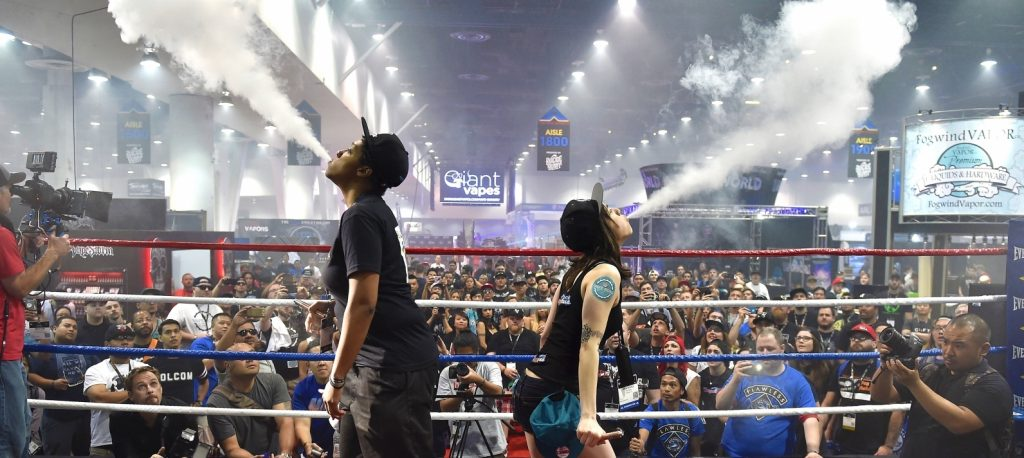 Two women are shown blowing clouds of smoke into the air with their backs to each other. Behind them is a large crowd of people.